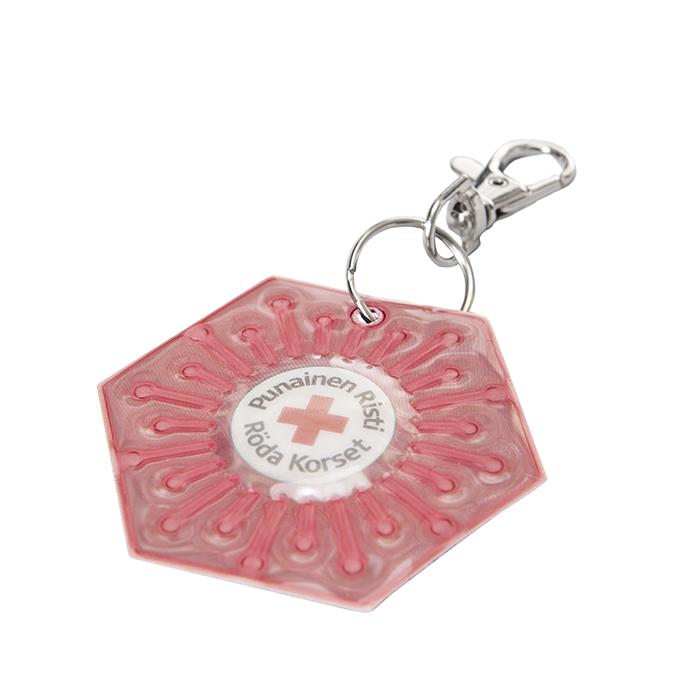 Kuusikulmaisen heijastimen keskellä on Punaisen Ristin tuotetunnus.